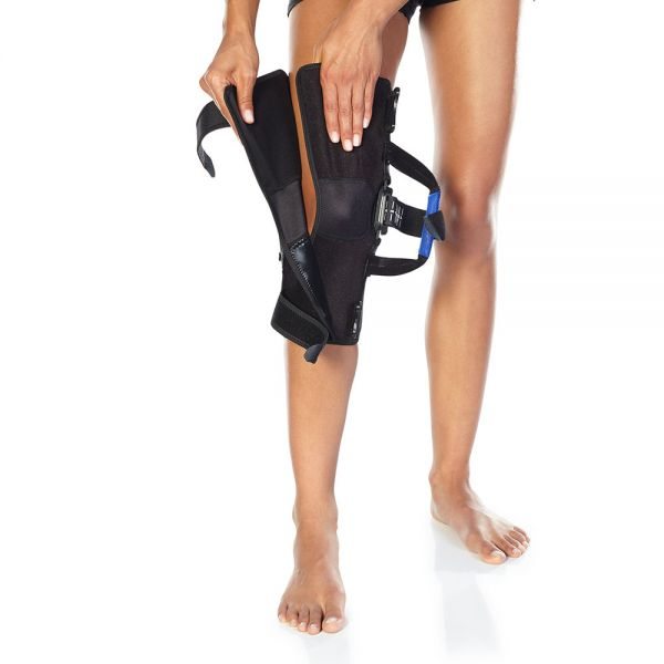 Hinged knee brace for patella tracking